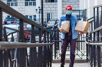 Man wearing a mask with food takeout bags