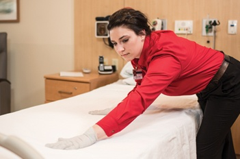 Hospital employee making a bed