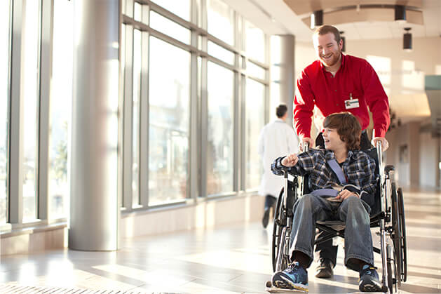 healthcare worker pushing male child in a wheelchair